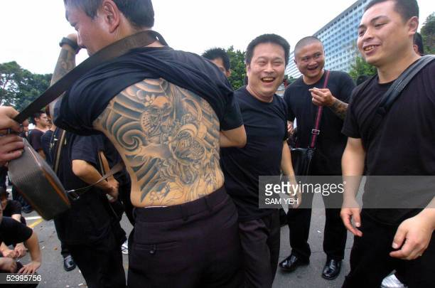 A local gangster displays his tattoo as others look on during the funeral of Taiwanese gang boss Hsu Hai Ching in Taipei 29 May 2005 Thousands of...