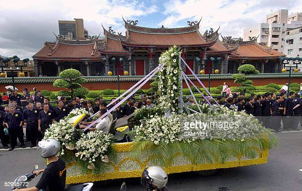 Local gangsters bow as the decorated funeral carriage for Taiwanese gang boss Hsu Hai Ching drives by in Taipei 29 May 2005 Thousands of gang members...