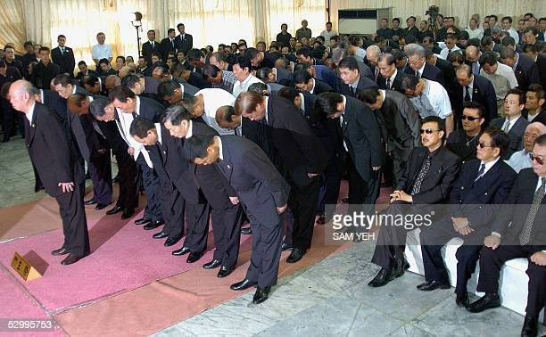 Local gangsters bow toward a portrait of Taiwanese gang boss Hsu Hai Ching during his funeral in Taipei 29 May 2005 Thousands of gang members...