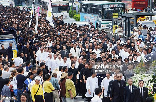 Local gangsters clad in black walk the streets after the funeral of Taiwanese gang boss Hsu Hai Ching in Taipei 29 May 2005 Thousands of gang members...