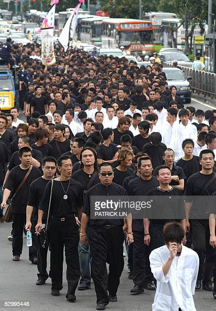 Local gangsters clad in black walk the streets in a procession after the funeral of Taiwanese gang boss Hsu Hai Ching in Taipei 29 May 2005 Thousands...