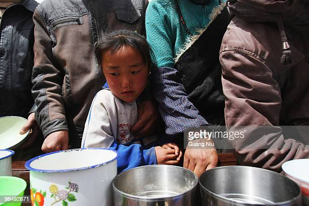 Local girl queues with adults at a food shelter on April 16, 2010 in Jiegu, near Golmud, China. It is currently reported that 791 people have died...