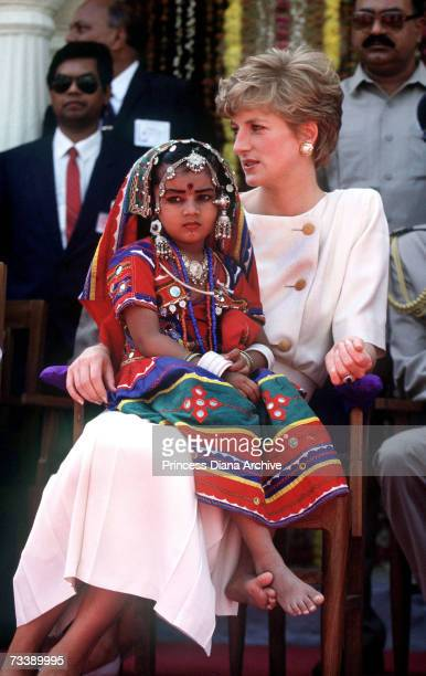 A local girl wearing traditional costume sits on the Princess of Wales' lap during her visit to Lallapet High School in Hyderabad India February 1992...