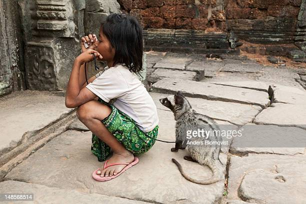 local girl with her pet palm civet at preah khan temple. - civet cat stock pictures, royalty-free photos & images