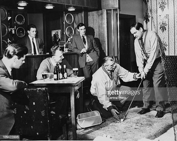 Local golfer Bob Midwood shows Jack Richardson how to hold a golf club in the cocktail bar of the Staincross Hotel, Barnsley, Yorkshire, 13th...