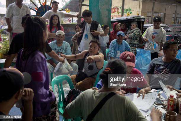 Local government employees distribute relief supplies at a temporary evacuation center at Balzain East Multi Purpose Center ahead of Typhoon...