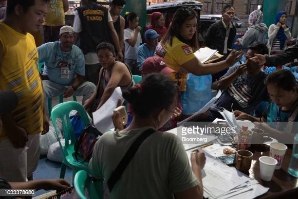 Local government employees work at a temporary evacuation center at Balzain East Multi Purpose Center ahead of Typhoon Mangkhut's arrival in...