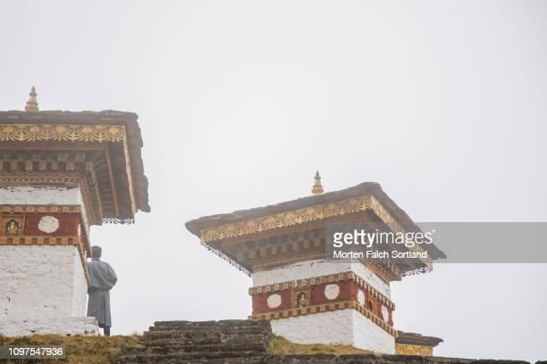 a local guide at the chortens of the dochula mountain pass in dochula, bhutan springtime - dochula pass stock-fotos und bilder