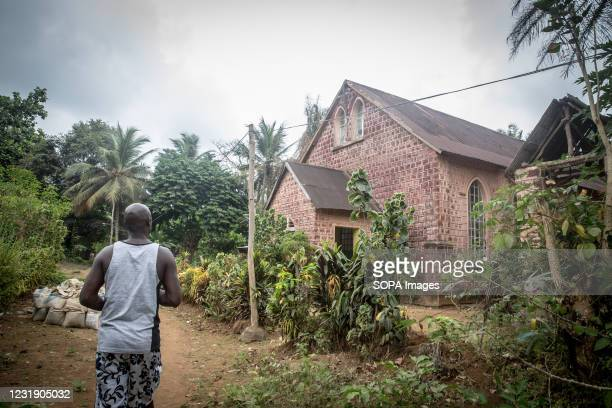 Local guide passes a Zion church on Sierra Leone's Banana Islands. The Banana Islands were once a slave trading port. They are now home to a few...