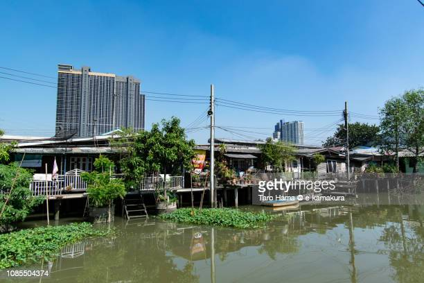Local houses on Chao Phraya River and urban residential building in Nonthaburi Province in Thailand