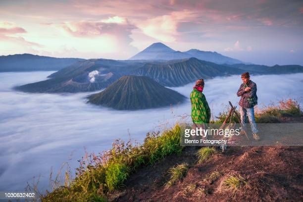 2 local indonesian doing campfire while sunrise with mt.bromo in background - bromo tengger semeru national park stock photos and pictures