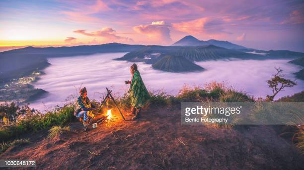 2 local indonesian doing campfire while sunrise with mt.bromo in background - java indonesia fotografías e imágenes de stock