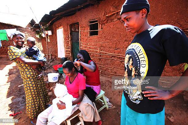 Local inhabitants coming together for hairstyling in Kibera Slum on March 20 2009 in Nairobi Kenya A woman is wearing a tshirt with the Barack Obama...