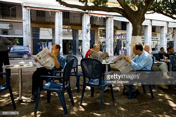 Local inhabitants read the morning paper at a cafe on Revolution Street in what was formerly Cours Bertagna in the city center of Annaba