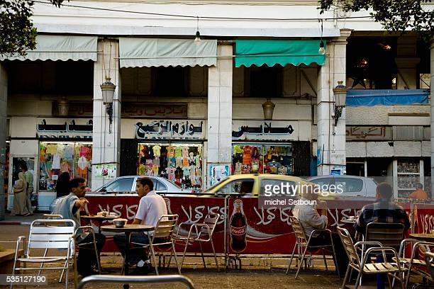 Local inhabitants sit at a cafe on Revolution street formerly Cours Bertagna in the city center