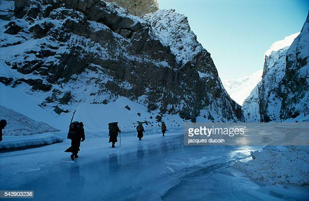 Local inhabitants walk the frozen surface of the Zanskar River