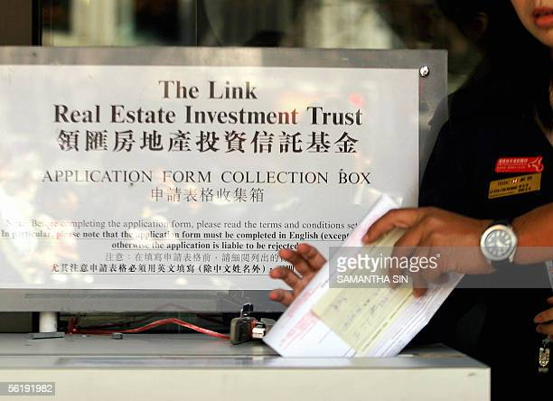 A local investor drops an application form for Link Real Estate Investment Trust into a collection box outside the Hong Kong Bank during the last day...