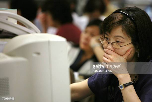 A local investors looks at the stock market index online at a securities firm in Hong Kong 06 August 2007 The Hang Seng Index closed down 60171...