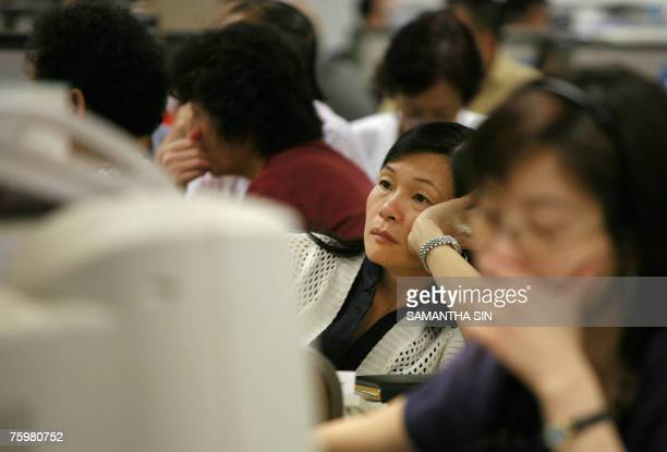 Local investors looks at the stock market index online, at a securities firm in Hong Kong, 06 August 2007. The Hang Seng Index closed down 601.71...