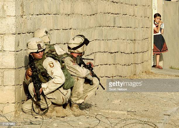 A local Iraqi girl watches from the doorway of her home as US Army 101st Airborne troops take cover July 23 2003 near the site where they killed both...