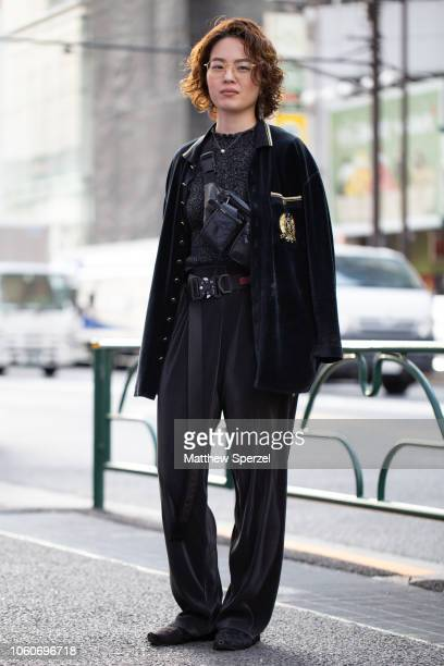 A local is seen on the street in Harajuku wearing velvet jacket with gold emblem grey sweater black crossbody bag and pants with Alyx belt on October...