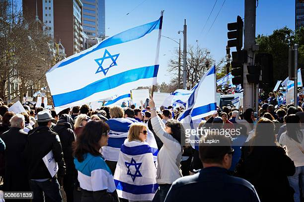 Local Jewish community wave Israeli flags and wrap the flags around their bodies at a proIsrael rally outside Parliament house in Melbourne on 10...
