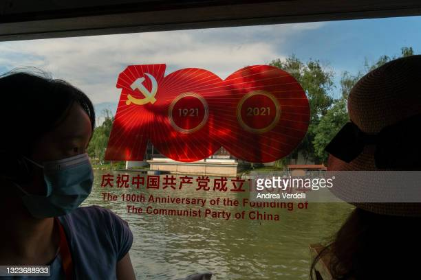 Local journalists sit on a boat with a sign commemorating the 100th anniversary of the founding of the Communist Party of China, stamped on the...