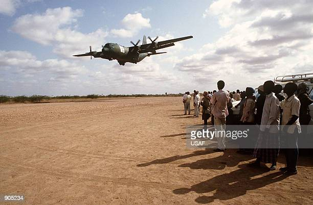 Local Kenyan workers watch a C130 Hercules from the 314th Airlift Wing Little Rock AFB Arkansas deliver relief supplies to Wajir Kenya The C130 and...