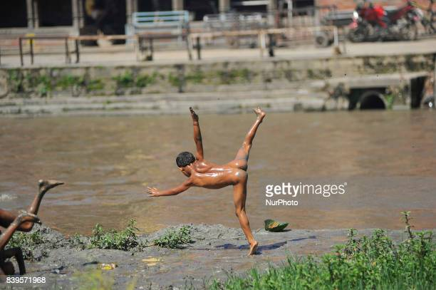A Local kid playing with mud and somersault around Bagmati River at the premises of Pashupatinath Temple at Kathmandu Nepal on Saturday August 26 2017