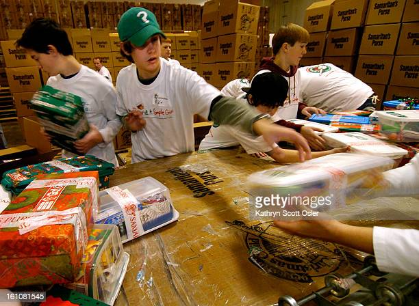 AURORA CO NOV 28 2006 Local kids families and other volunteers work in a large warehouse in Aurora to prepare 400000 giftfilled shoe boxes for...