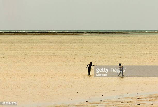 Local Kids Playing Football in Shallow Water
