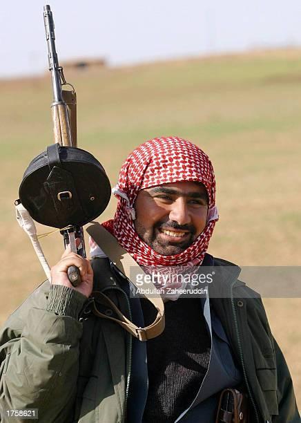 A local Kurdish fighter raises his gun February 3 2003 in the village of Pir Daud south of Erbil the de facto capital of northern Iraq Kurdish...
