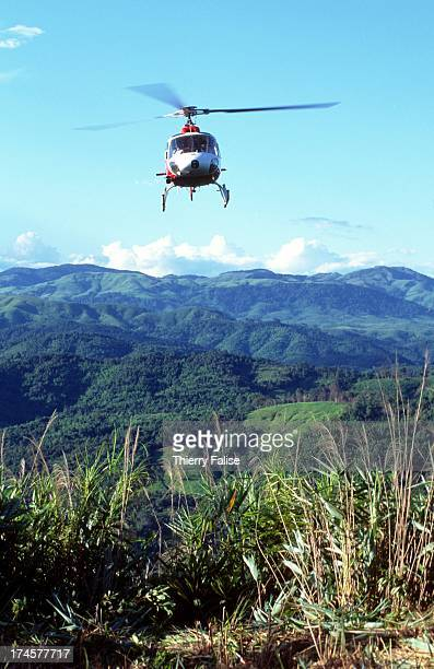 Local Lao villagers are carried by helicopter to the top of a hill where they are assigned to clear a landing zone and a track into the jungle where...