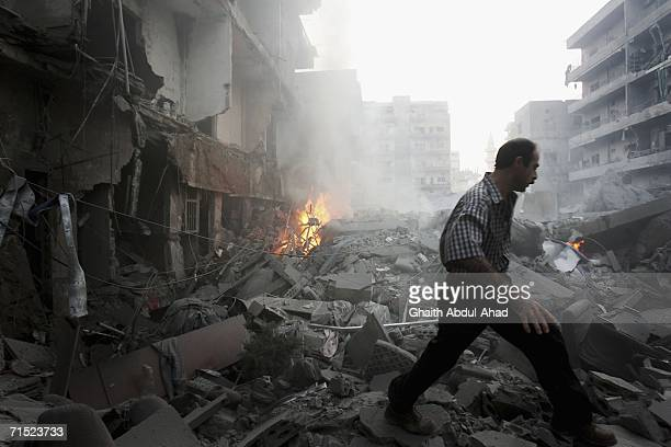 Local Lebanese try to extinguish the fire after an Israeli air strike hit a cultural centre affiliated with Hezbollah July 26, 2006 in the southern...