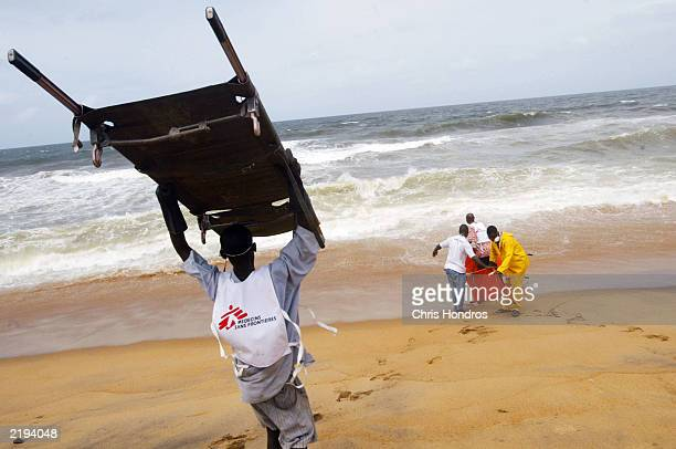 Local Liberian staffers with Doctors Without Borders wash off gurneys in the ocean after carrying bodies to mass graves dug on the beach for patients...