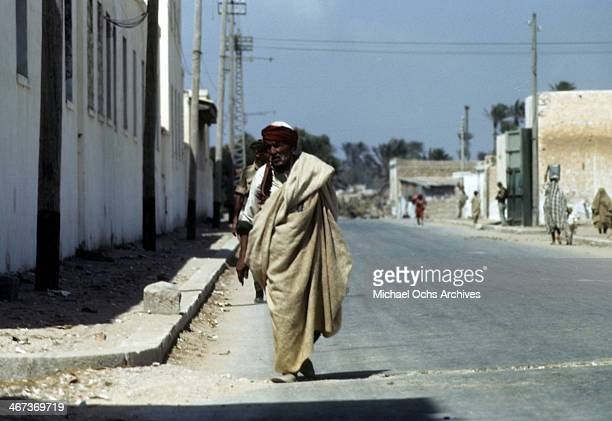 A local Libyanese man wearing regional clothes walks down the street in Benghazi Libya