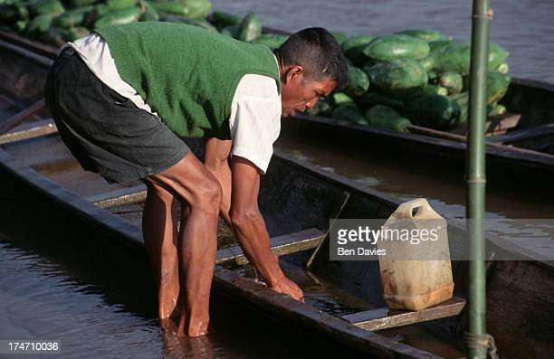 A local loads up his boat with papaya and other fruits on the Mekong River near the picturesque village of Sangkhom in Northeast Thailand The Mekong...