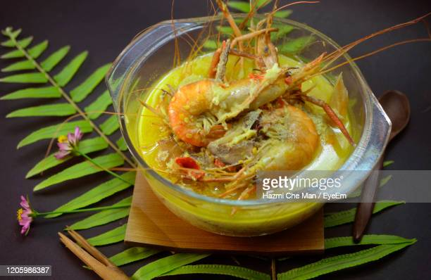 local malaysian dish.fresh watervprawn cooked with spice on coconut tumeric gravy - frische stockfoto's en -beelden