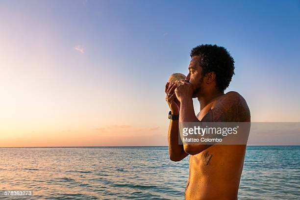 Local man blowing conch shell at sunset, Fiji