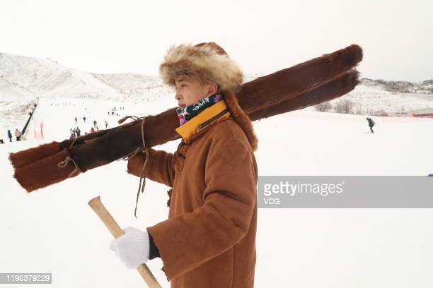 A local man carries ancient fur snowboard before skiing at a ski resort on November 27 2019 in Altay Xinjiang Uyghur Autonomous Region of China Local...