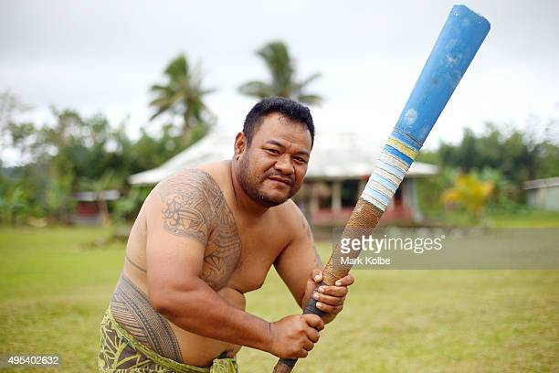 A local man from a small village in the Atua district of the Upolu island poses with a hand made cricket bat as they play a game of cricket on...