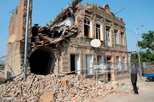 Local man Gambar looks at a residential building damaged by shelling during the ongoing military conflict between Armenia and Azerbaijan over the...