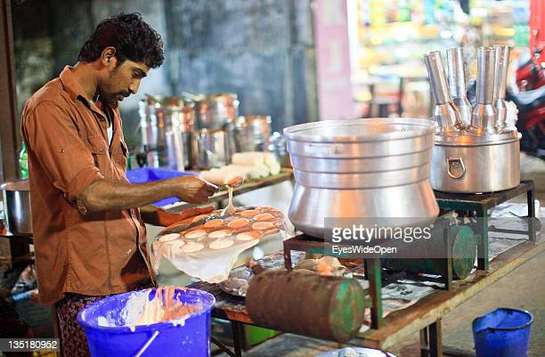 Local man is cooking Iddly a typical South Indian traditional food Kerala breakfast made from ricepowder on December 03 2011 in Guruvayur Kerala India