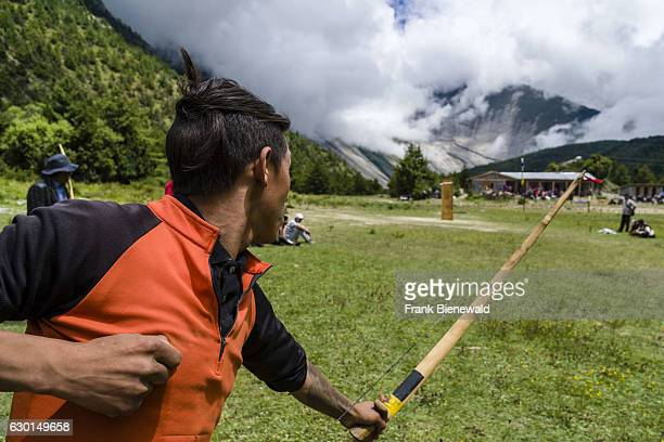 A local man is practising archery at a village festival in Upper Marsyangdi valley