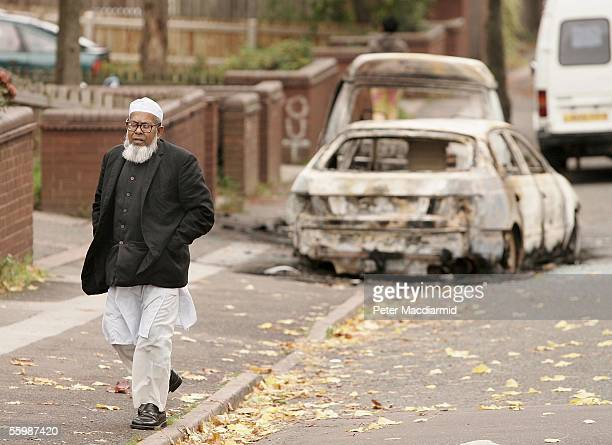 A local man is seen near burnt out vehicles in the Lozells area on October 23 2005 in Birmingham England Community leaders linked the disturbances in...