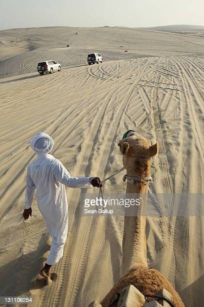 A local man leads tourists riding camels as fourwheel drive SUVs drive by along desert dunes that lead to the Khor al Adaid inlet of the Persian Gulf...