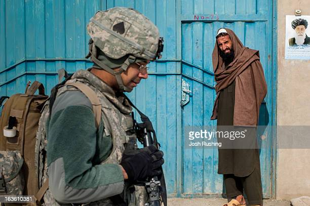 CONTENT] A local man looks on as US soldiers from the 506th Infantry patrol the streets of Maidan Shahr in Wardak Province Afghanistan President...