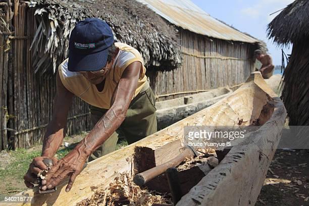 Local man making dugout canoe