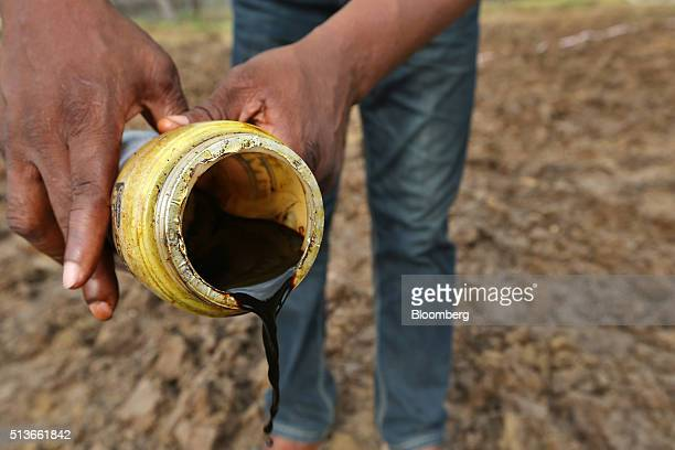 A local man pours a container of oil collected from the Bumo oil manifold site operated by Royal Dutch Shell Plc in KDare Nigeria on Wednesday Jan 13...
