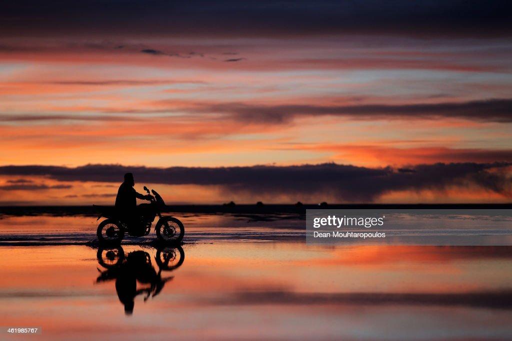 A local man rides his motorbike as the sun sets over the Salar de Uyuni of Uyuni Salt Flat during Day 7 of the 2014 Dakar Rally on January 11, 2014 in Uyuni, Bolivia.